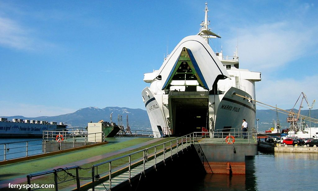 Larger car ferry with ramp ready to accept cars and vehicles