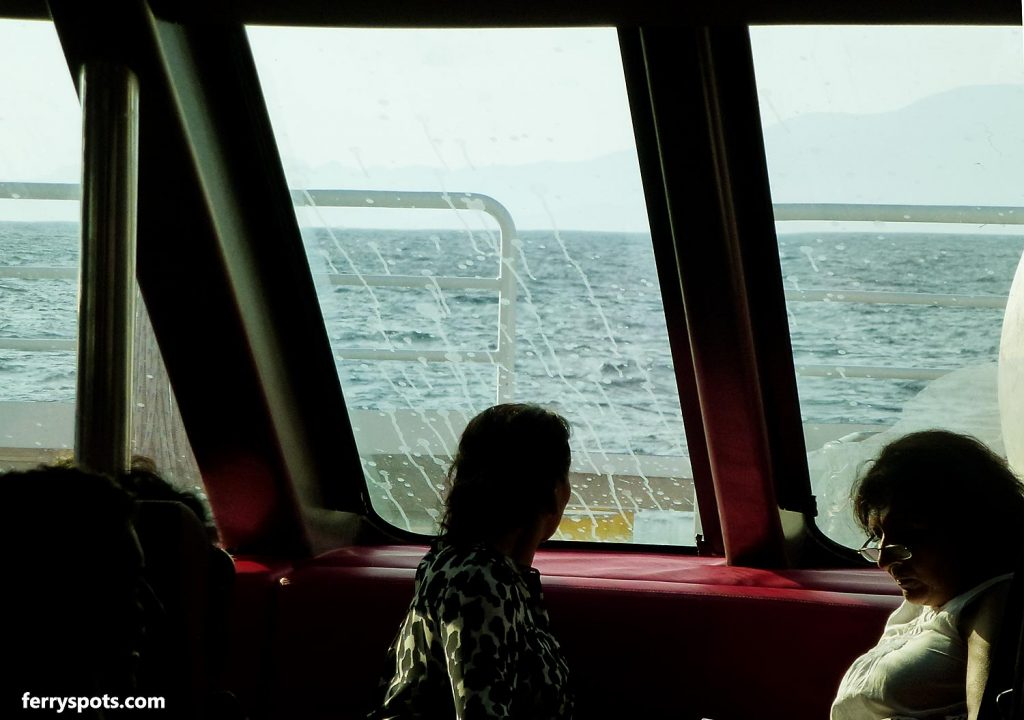 Cold and rainy day views from inside salon, passenger lounge on fast ferry